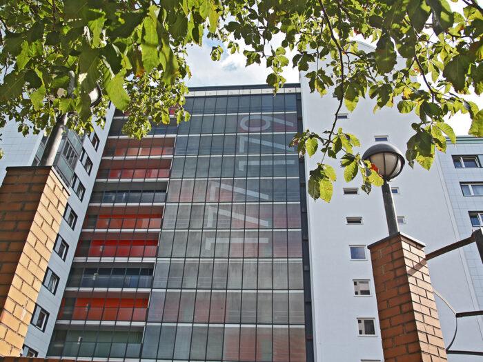 Folienbeklebung auf Glasfassade als Wegeleitsystem mit grossen Hausnummern